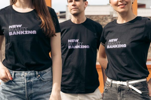 2 Frauen und 1 Mann, die Nuri (New Reality Banking) T-Shirts tragen. Urheberrecht: nuri.com